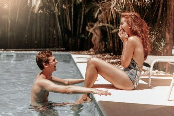 A Man in a pool and a woman sitting on the edge enjoying life after divorce.