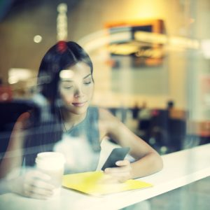 Cafe city lifestyle woman on phone drinking coffee because she learned to financially survive.