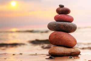 Client balance - Stones pyramid on sand symbolizing zen, harmony, balance. Ocean at sunset in the background