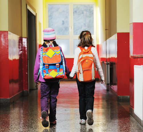 Two girls walk hand in hand down a school hallway. They accept their routines during a divorce.