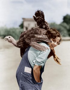 Personal growth means growing. This woman carries a turkey on her shoulder. The turkey is moving.