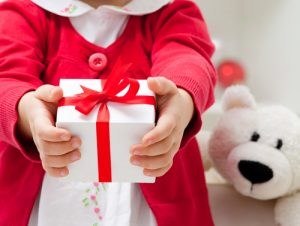 Find grace under the pressure of your divorce this holiday season by extending gifts instead of gossip. Like this little girl in red and white giving a present.