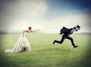 Crisis Mode - understanding what happens when a marriage breaks up, a woman wearing a wedding dress is reaching for a man, in a tux, running away.