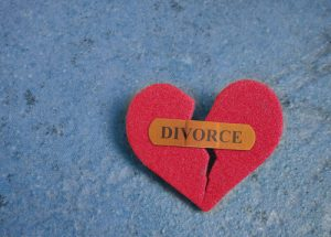 A broken heart with the word divorce on it begin the process of divorce.