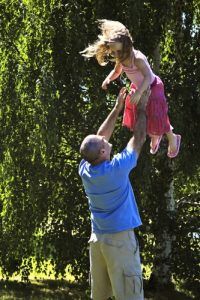 A dad is a male role model for his daughter as he tosses her up in the air.