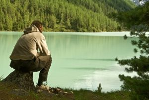 A man sitting near the lake working to mend a broken heart.