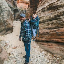 The best parenting advice for single dads is enjoy your kids like this dad carrying his child on a backpack hiking in a canyon.