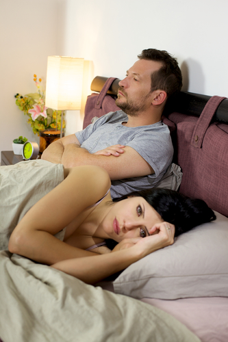 A man sits upright in bed reconciling his wife's infidelity as she lies next to him.