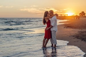Marriages survive infidelity with passion as a man and woman hug each other on a beach at sunset.