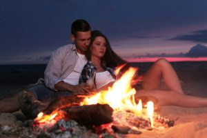A couple falling in love on the beach at sunset with a campfire on the sand.