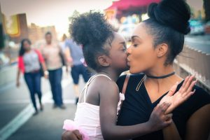 Being a divorced, single mom, a woman kisses her child on the cheek on the street.