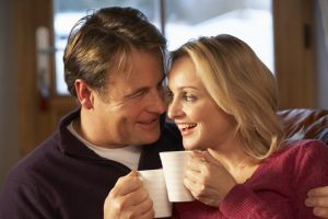 A middle aged couple sitting with coffee show what women need for courtship after a divorce.