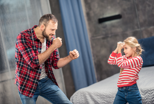 Being a single dad, a man in a plaid shirt plays with his daughter.