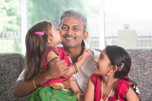 A man hugs his two daughters while being a single dad.
