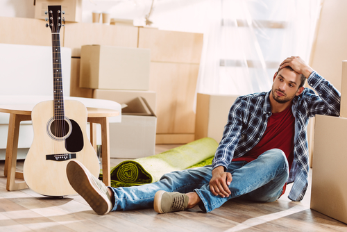 Man moving out of the family home is sitting on the floor surrounded by boxes and a guitar with his head in his hand.