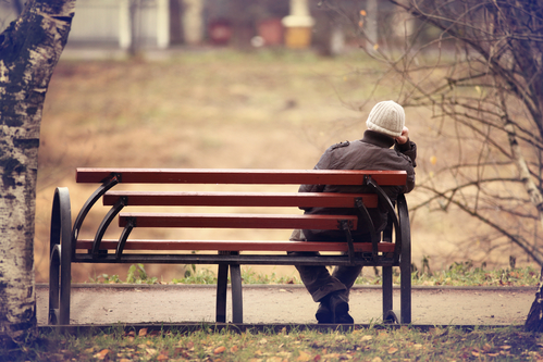 Person sitting on an out door bench looking at an autumn scene considering if they're worthy of love.