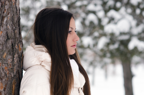 A woman wearing a white coat leans against a snow covered tree wondering, 'how do you end your marriage?'