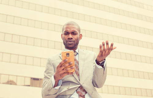 A black man looking annoyed while reading his cell phone.