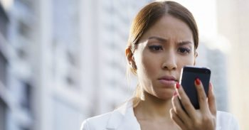 A woman staring at her phone thinks it's time to time to start blocking people.