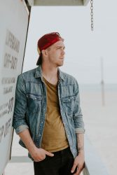 Man wearing a red baseball cap backwards coping with depression due to divorce leaning on a sign looking at the beach.
