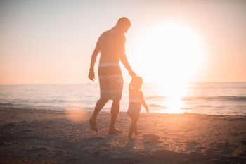 A Man Adjusting To Being A Single Dad Holding His Child's Hand Walking On The Beach.