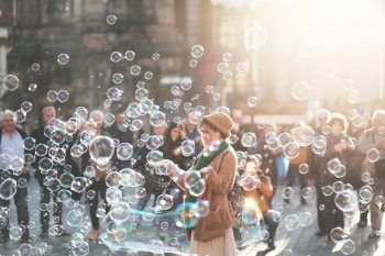 Woman surrounded by bubbles not thinking about her divorce for a while