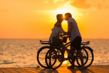 A man and woman on a beach at sunset kissing, learning coping skills when dealing with divorce.