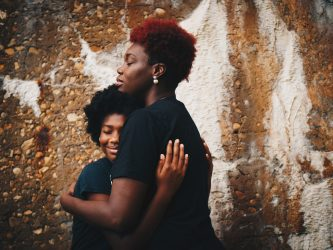 A black teenager hugging her mother coping with a divorce in the family.
