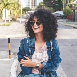 A woman with curly hair being a sexy single mom standing on a corner with a big smile on her face.