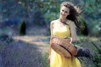 A woman in a yellow dress exemplifies life after divorce by walking through a field of lavender.