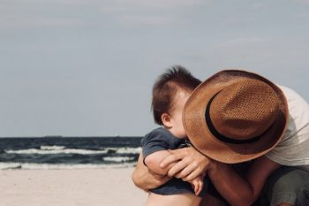 A single dad kisses his baby on the beach