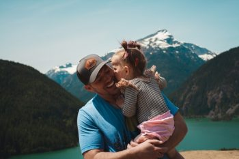 Coping with divorce as single fathers, a man holds his daughter in front of a snow capped mountain.