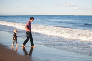 Dad learning to overcome pain of separation walks with son on beach.
