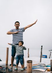 A boy and a man make large arm gestures pointing in opposite directions on a dock.