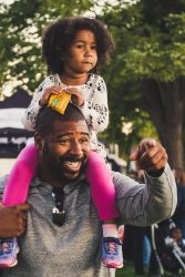 A happy dad carries his daughter on his shoulders.