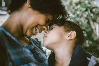 A mom and a boy rub noses.