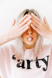 Blond haired woman with hands over eyes dealing with daily overwhelm.