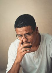 A dark skin man w glasses is annoyed by the foolish complaining at his office.